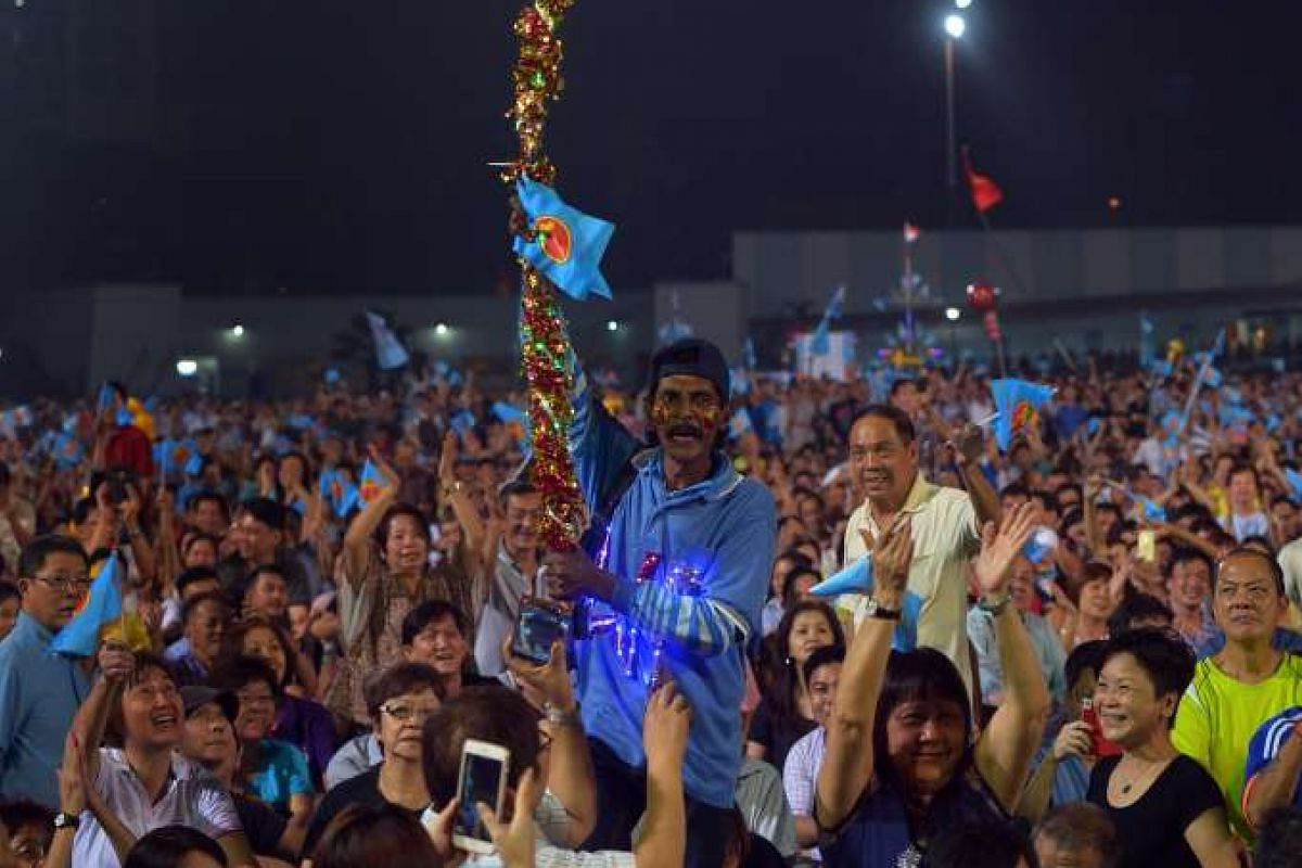 A supporter holds up a handmade totem at the Workers' Party rally for Aljunied GRC at the Serangoon Stadium on Sept 8, 2015.