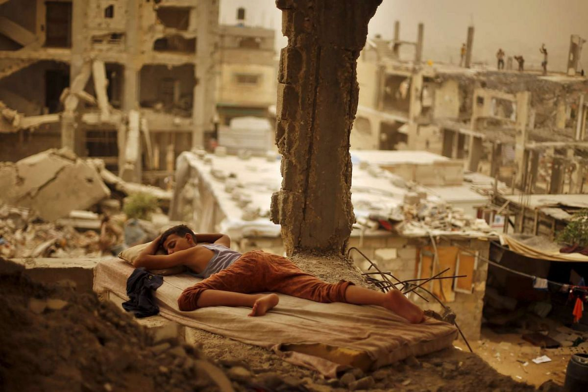 A Palestinian boy sleeping on a mattress inside the remains of his family's house that witnesses said was destroyed by Israeli shelling during a 50-day war in the summer of 2014, during a sandstorm in Gaza on Sept 8, 2015. PHOTO: REUTERS / SUHAIB SAL