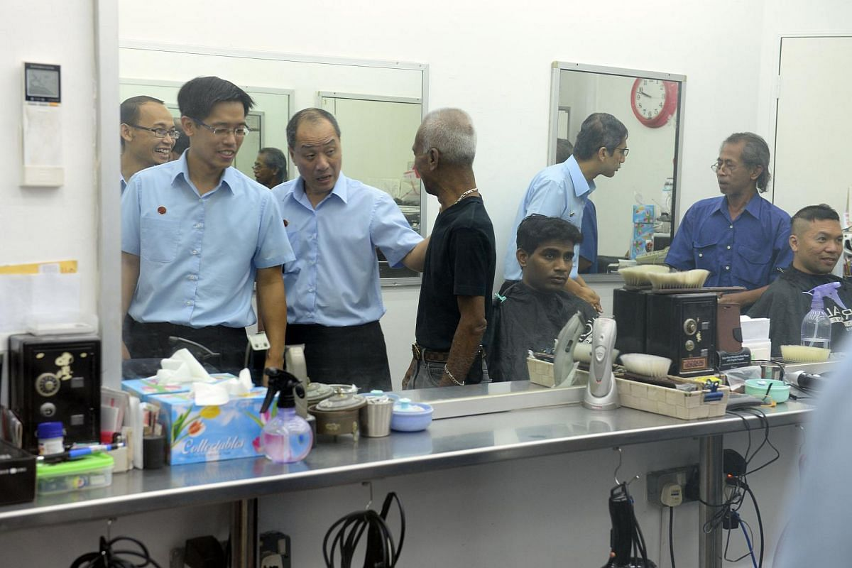 Mr Low Thia Kiang (third from left), secretary-general of Workers' Party with East Coast GRC (from left), Mohamed Fairoz, Gerald Giam and Leon Perera (far right) visit a barber shop during their walkabout at Simei on Sept 8, 2015.