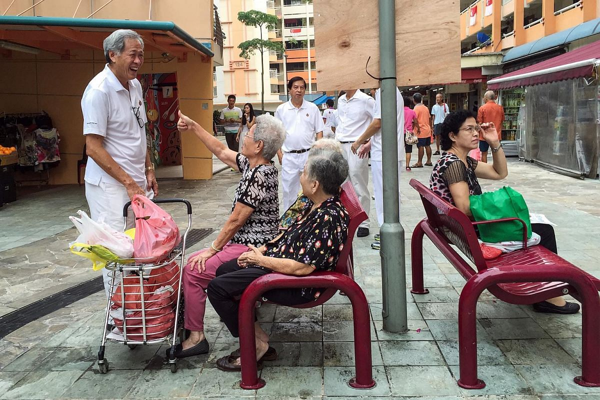 Dr Ng Eng Hen (left), PAP's candidate and anchor for Bishan-Toa Payoh GRC,chatting with residents outside the market and food centre at Block 127 Toa Payoh Lorong 1 on Sept 8, 2015.
