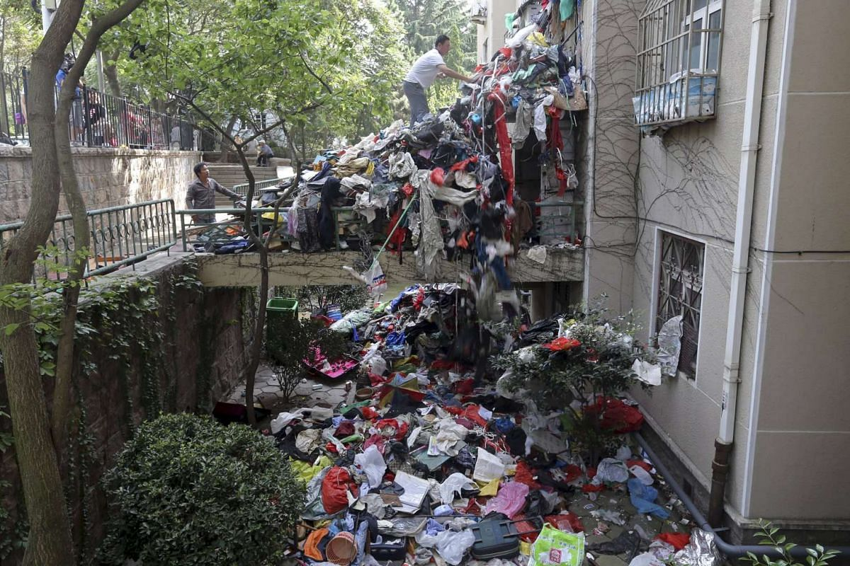 A pile of garbage blocks an entrance to a residential building as workers clean up one of its apartments, in Qingdao, Shandong province, China, on Sept 9, 2015. The authorities are acting on persistent complaints from the surrounding residents due to