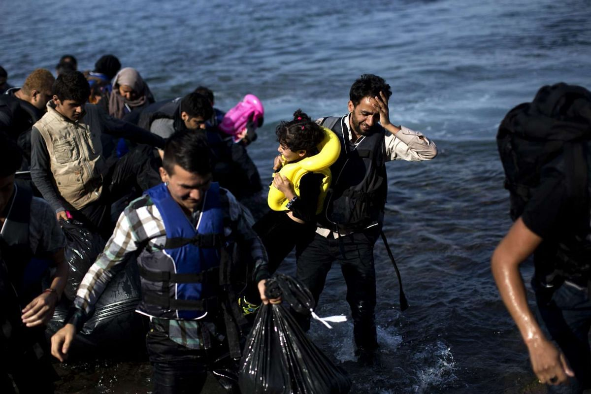 Migrants arriving on the shores of the Greek island of Lesbos after crossing the Aegean Sea from Turkey on a dinghy on Sept 9, 2015. PHOTO: AFP/ANGELOS TZORTZINIS