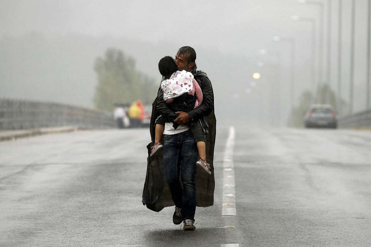 A Syrian refugee kissing his son as he walks through a rainstorm towards Greece's border with Macedonia, near the Greek village of Idomeni, on Sept 10, 2015. PHOTO: REUTERS/YANNIS BEHRAKIS