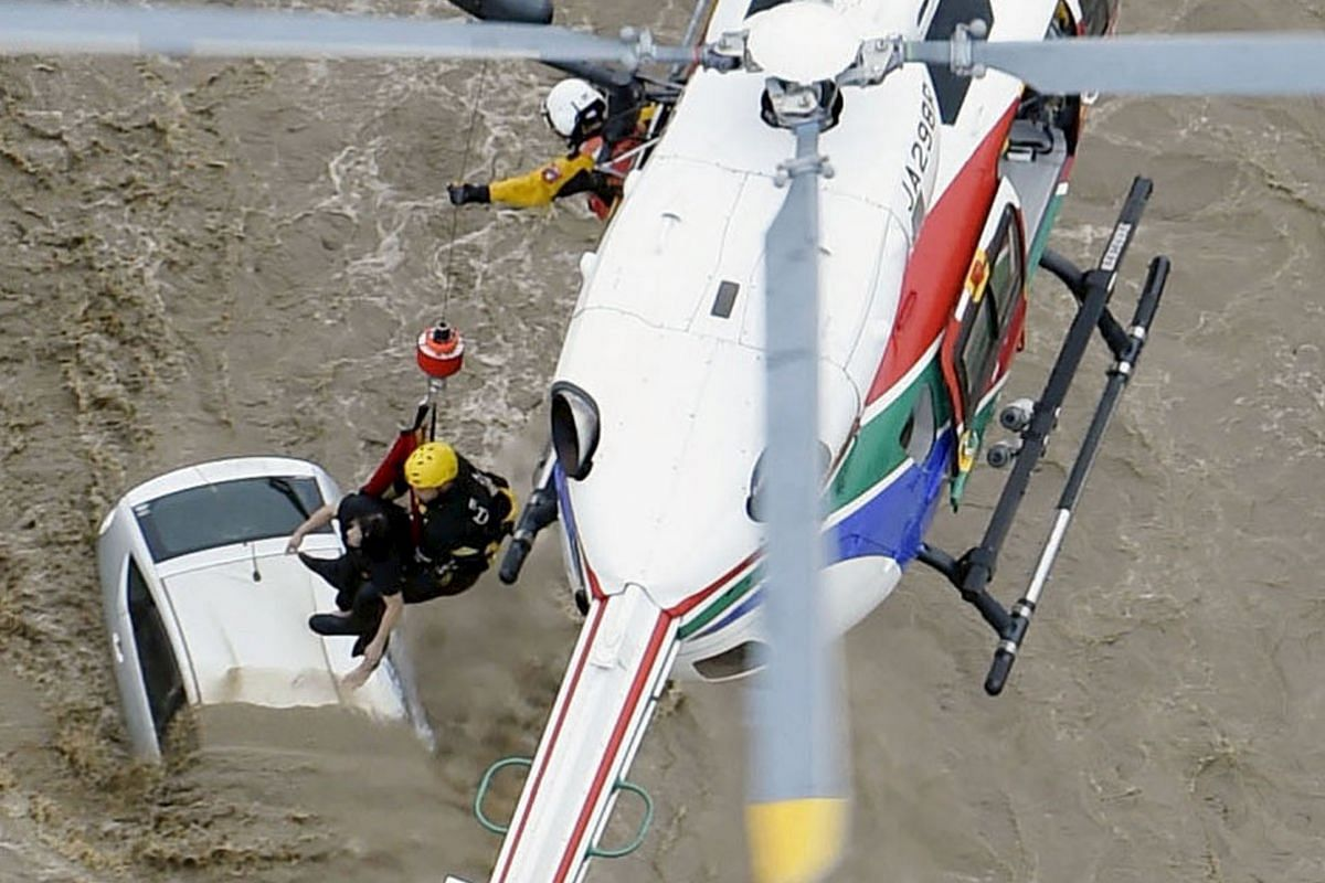 A resident being winched up by a rescue helicopter at a residential area flooded by the Kinugawa river, caused by Typhoon Etau, in Joso, Ibaraki prefecture, Japan, on Sept 10, 2015.