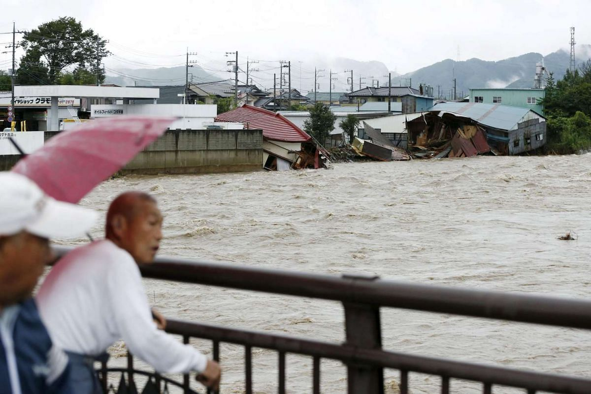 Local residents looking at damaged houses and the flooded Kurokawa river, caused by Typhoon Etau in Kanuma, Tochigi prefecture, on Sept 10, 2015.