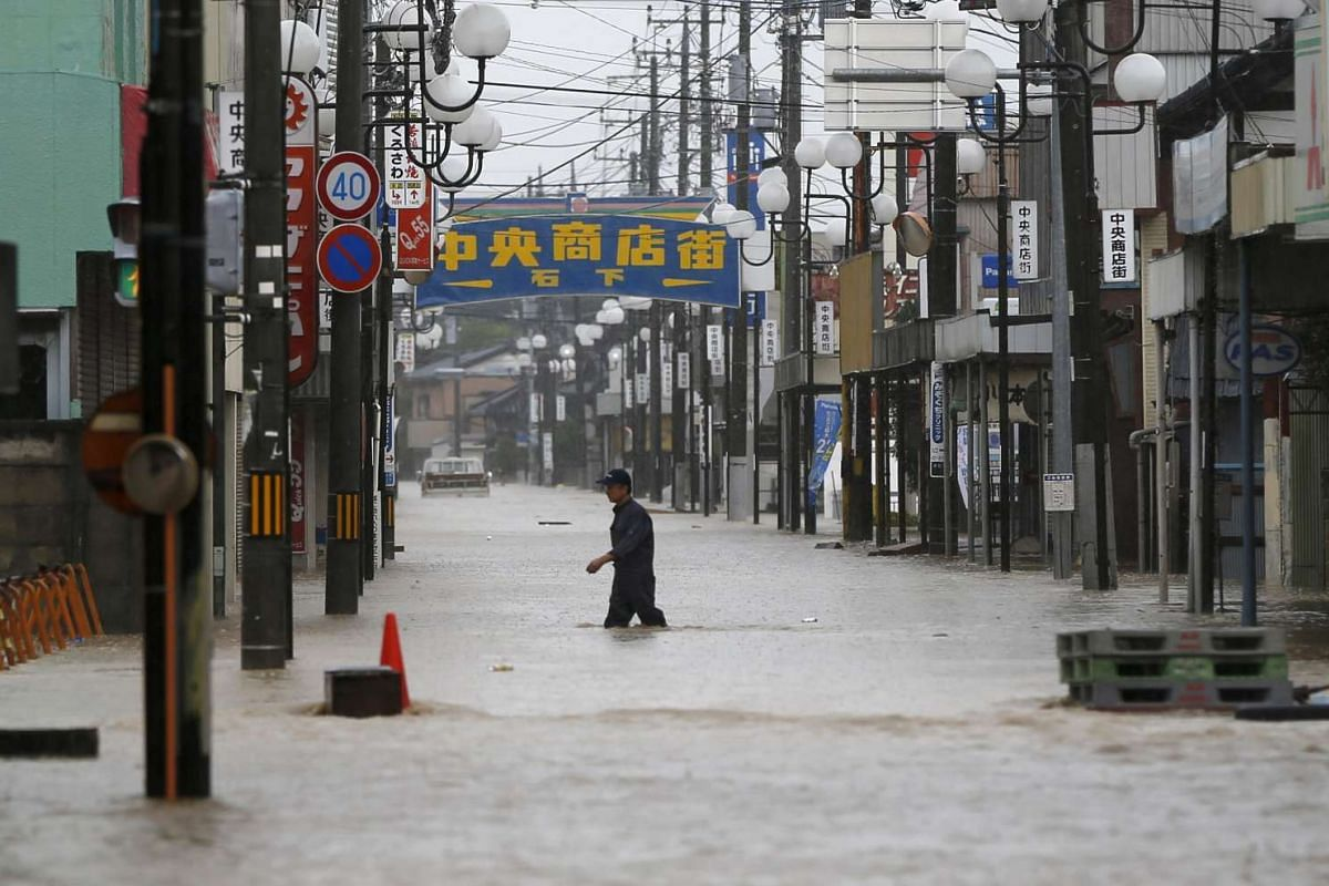 A man wading through a local shopping area flooded by the Kinugawa river, caused by Typhoon Etau, in Joso, Ibaraki prefecture, Japan, on Sept 10, 2015.
