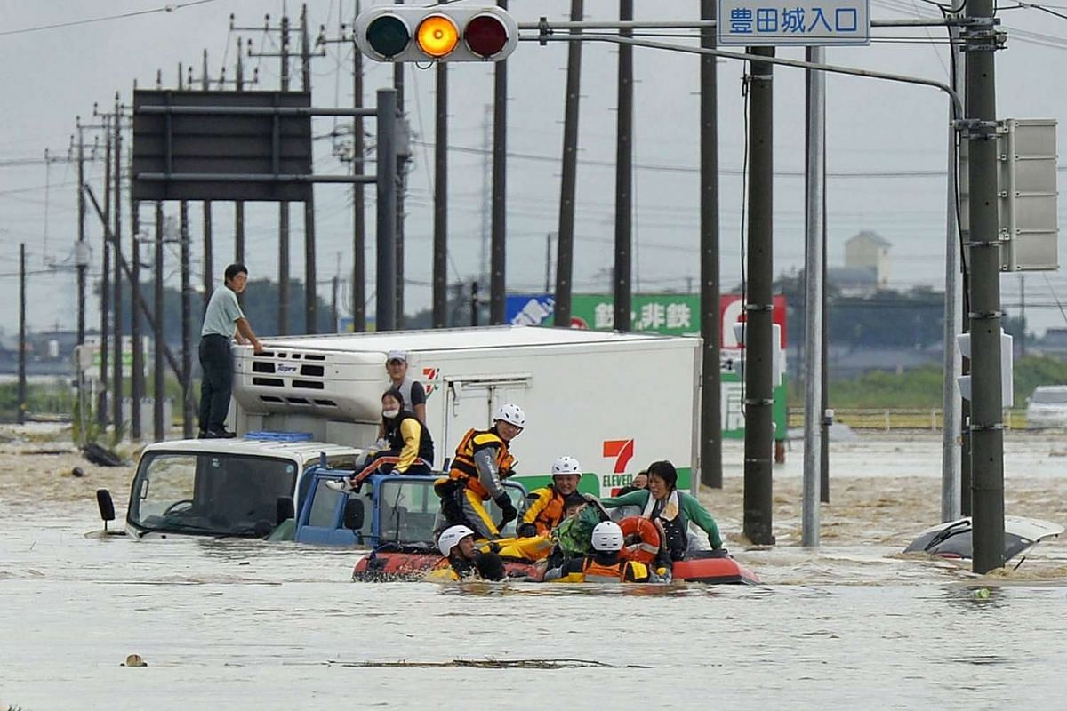People being rescued from vehicles by firefighters at an area flooded by the Kinugawa river, caused by Typhoon Etau, in Joso, Ibaraki prefecture, Japan, on Sept 10, 2015.