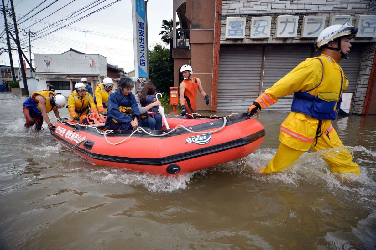 Rescue workers transporting evacuees in a rubber boat through floodwaters at Oyama in Tochigi prefecture, north of Tokyo, on Sept 10, 2015.