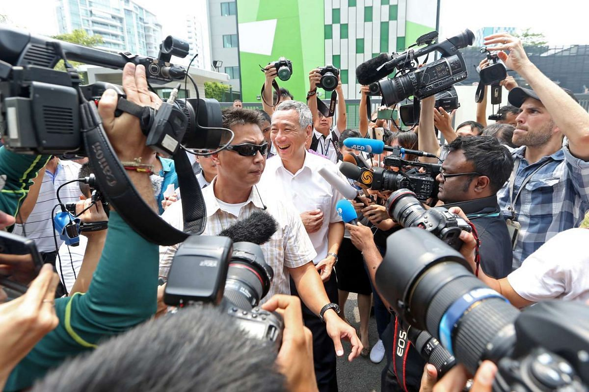 PM Lee Hsien Loong is surrounded by the media as he leaves Alexandra Primary School after casting his vote.