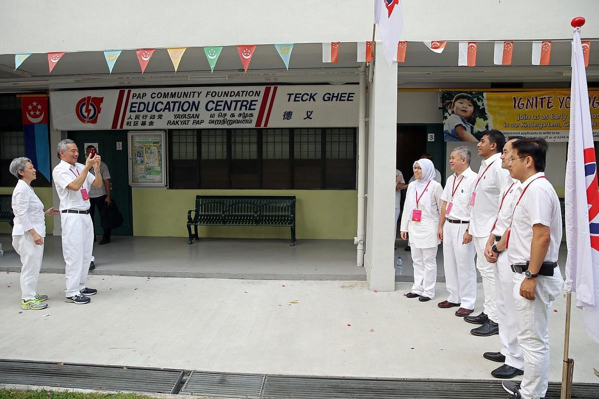 PM Lee Hsien Loong and People's Action Party candidates for Ang Mo Kio GRC take a group photo before setting off from Block 322 Ang Mo Kio Avenue  3 to visit six polling stations across their GRC on Sept 11, 2015.