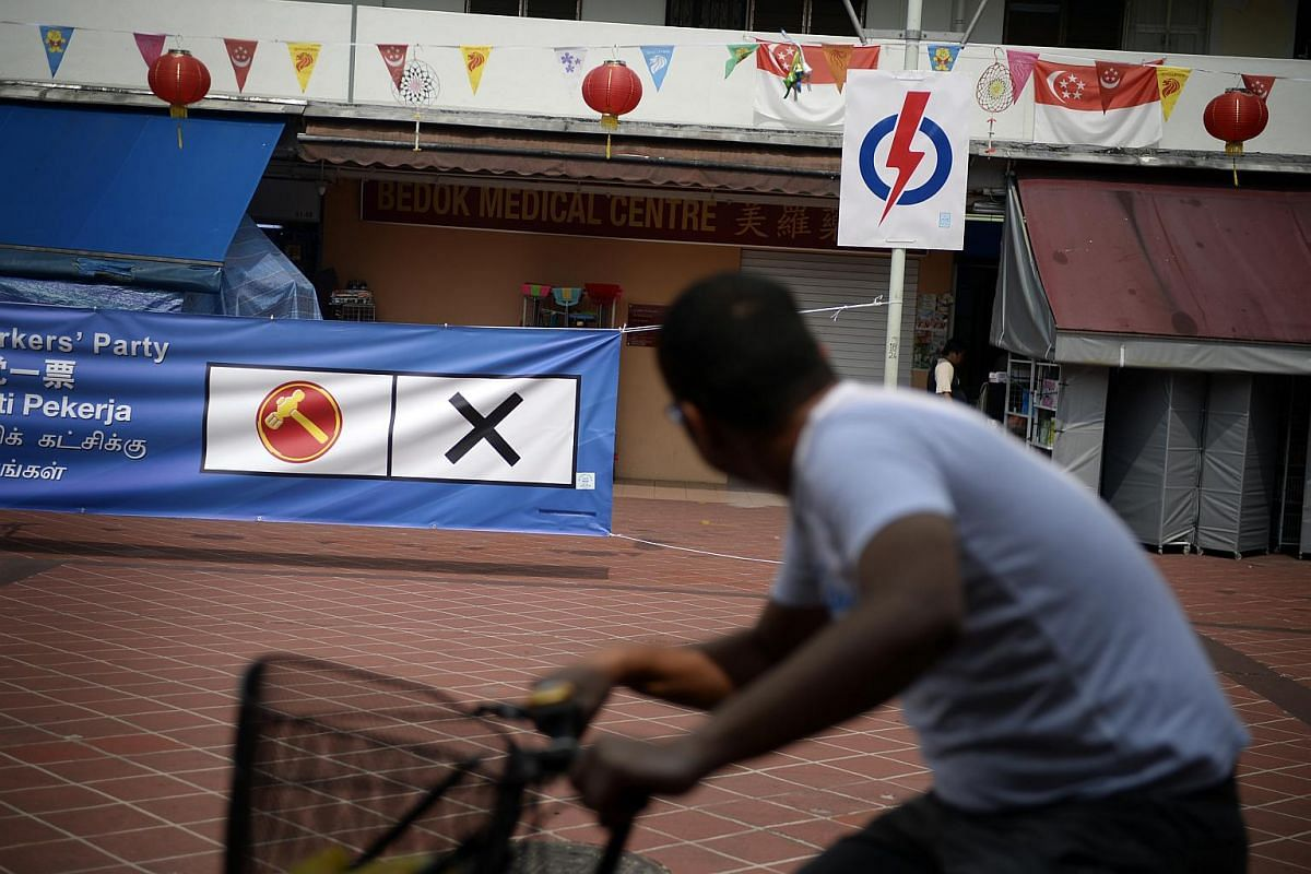 A Workers' Party (WP) banner and People's Action Party banner seen side-by-side outside Block 16 Bedok South Road food centre during a WP walkabout in the East Coast GRC on Sept 6, 2015.