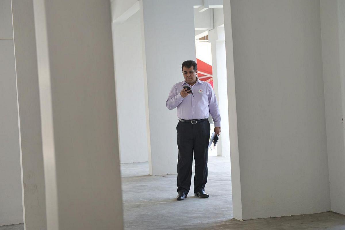 Ravi Philemon prepares himself before announcing his manifesto at a HDB void deck in Bukit Batok West.