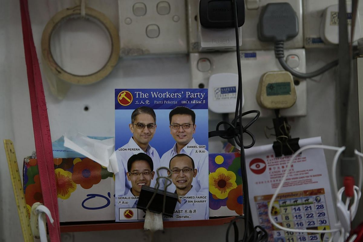 The faces of Workers' Party candidates for East Coast GRC - Mr Gerald Giam, Dr Daniel Goh, Mr Fairoz Shariff, and Mr Leon Perera - are seen on a flyer at a stall at New Upper Changi Road Market and Food Centre.