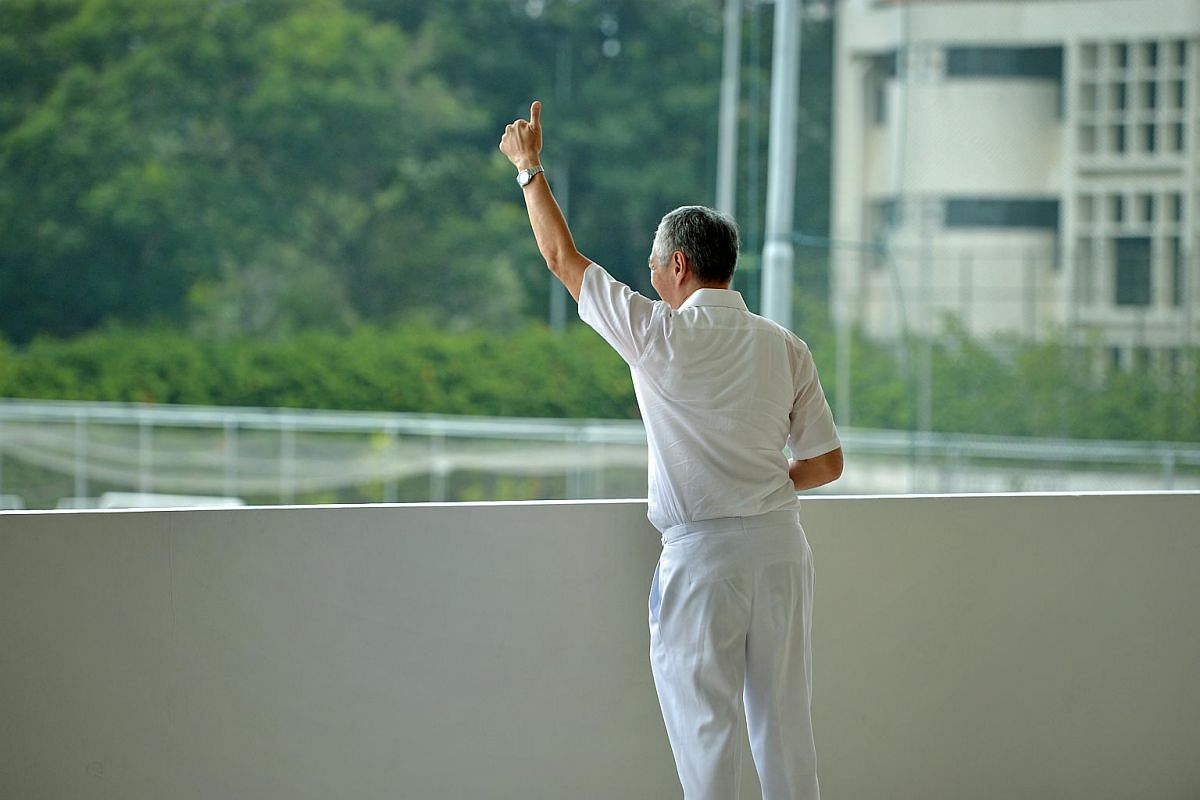PM Lee Hsien Loong gives his supporters the thumbs up before nomination hour at Raffles Institution on Sept 1, 2015.