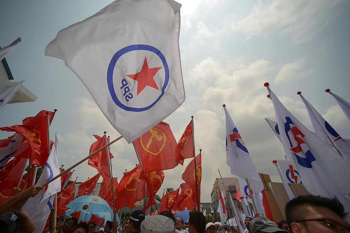 Flags representing the Singapore People's Party, Workers' Party and People's Action Party flutter on Nomination Day at Kong Hwa School on Sept 1, 2015.