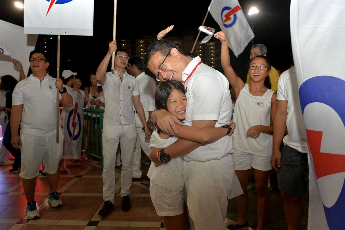 Marine Parade candidate Edwin Tong hugs his daughter Audrey, 9, as his other daughter Claire, 14, cheers him on.