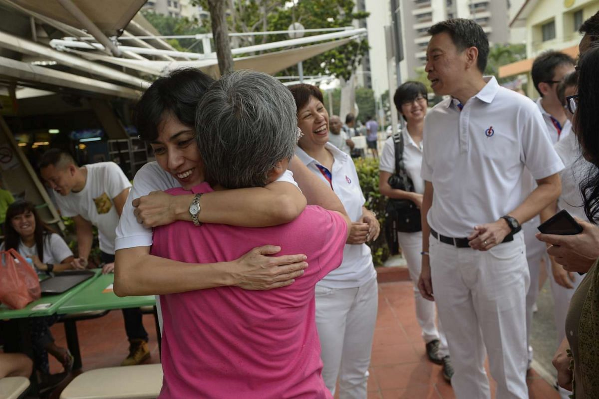 MP-elect for Tanjong Pagar GRC Joan Pereira hugs a resident while visiting Tanglin Halt market with Ms Indranee Rajah (centre) and Mr Melvin Yong (right) on Sept 12, 2015.