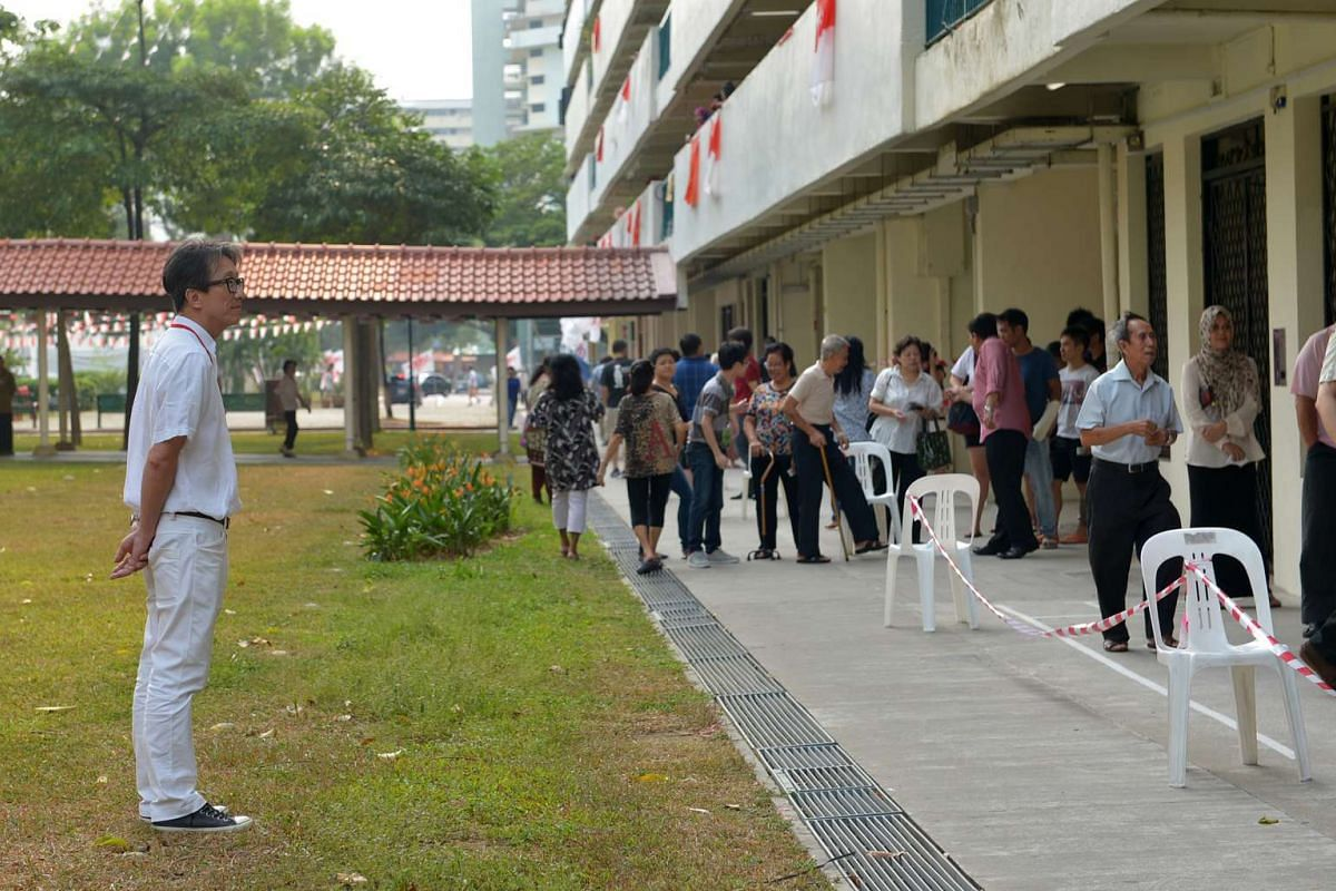 Mr Lim Swee Say looking at the voters at New Upper Changi Road polling station on Sept 11, 2015.