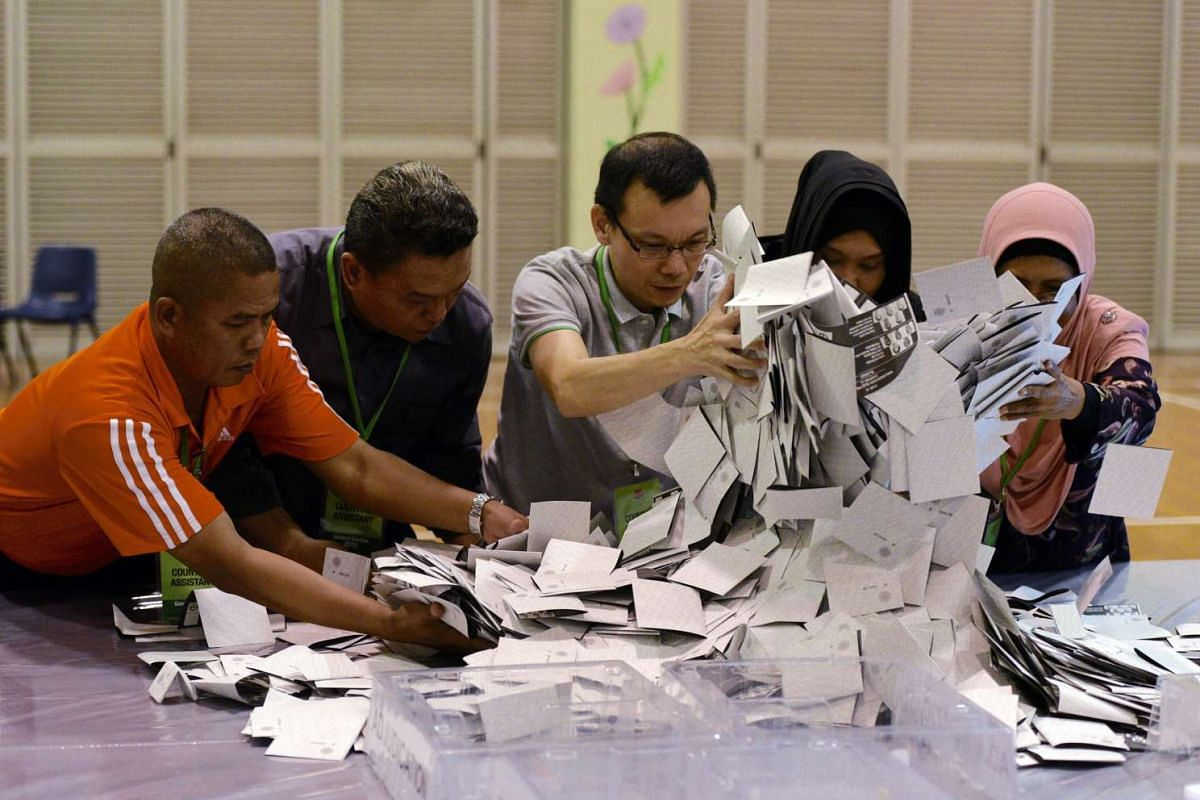 Counting assistants pouring out ballots from boxes which arrived at Bedok Town Secondary School.