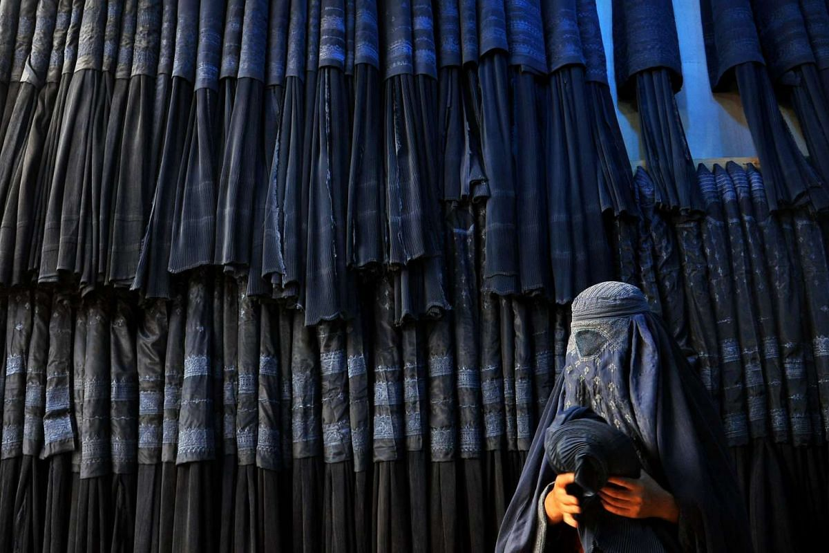 An Afghan woman buying a traditional burqa at a shop in Mazar-i-Sharif, Afghanistan. The burqa is a traditional Muslim women's dress consisting of an all-over veil and headscarf, with only a slit for the eyes. A full burqa also covers the eyes with a