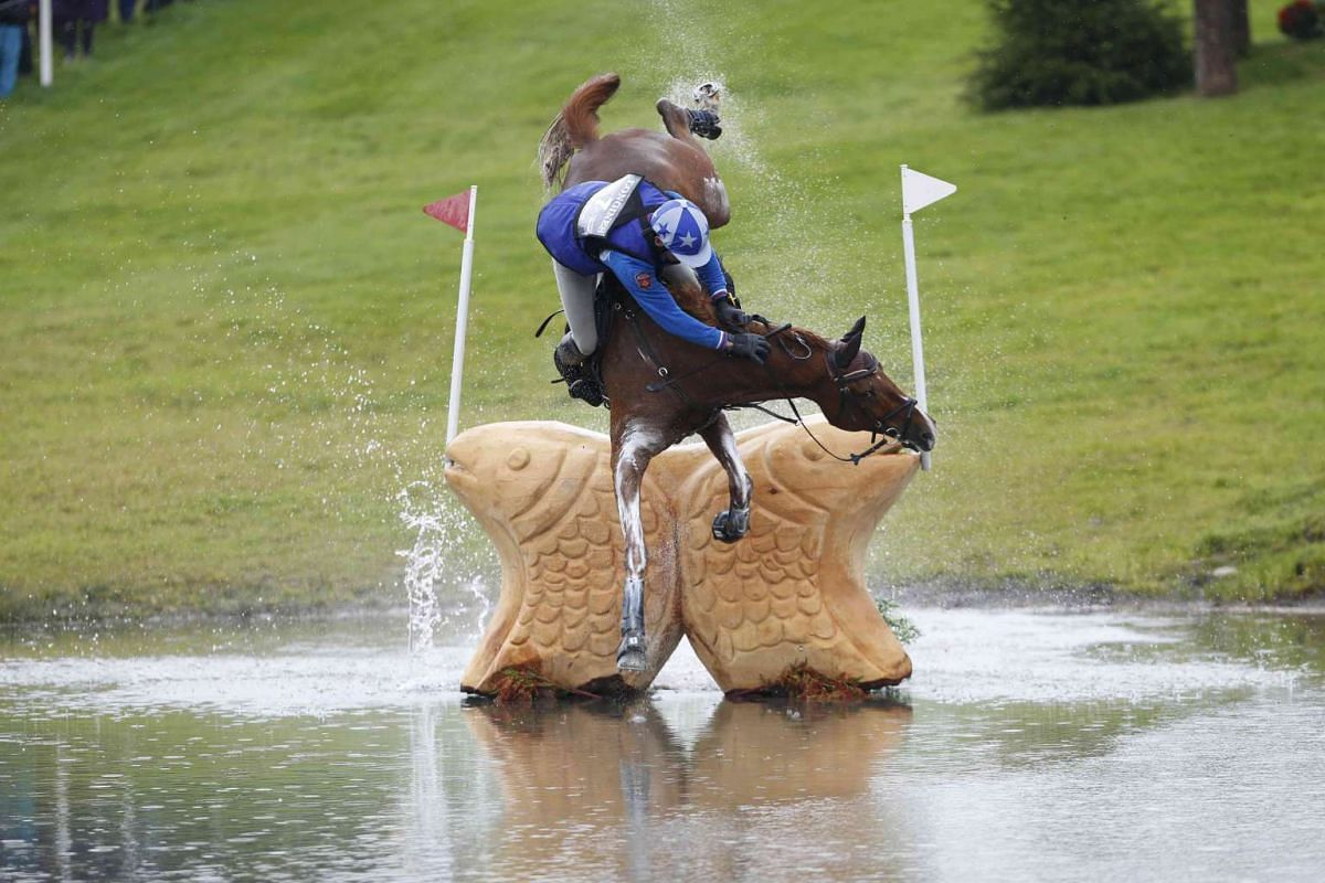 Russia's Mikhail Nastenko riding Reistag falls at the Lochan fence in the cross country event of the FEI European Eventing Championship at Blair Castle in Scotland on Sept 12, 2015.