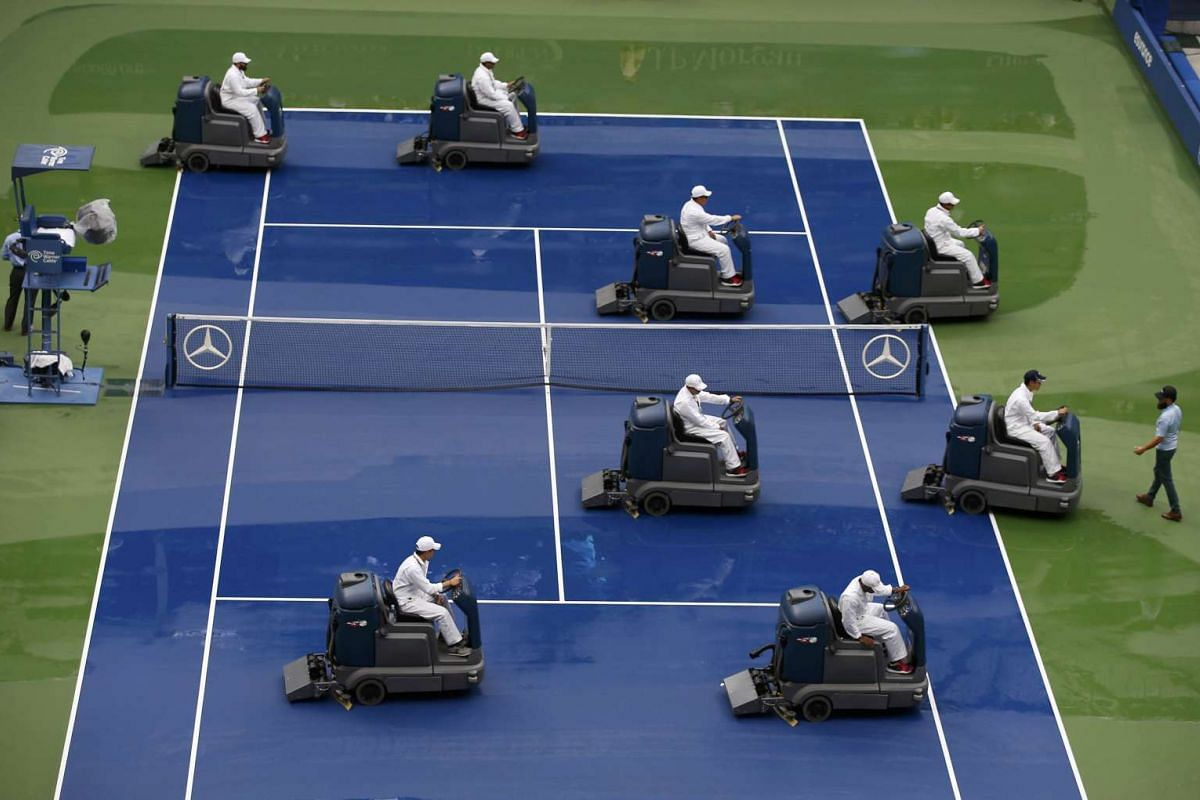Workers using equipment to dry the court after rain delayed the start of the men's singles final match between Roger Federer of Switzerland and Novak Djokovic of Serbia at the US Open Championships tennis tournament in New York on Sept 13, 2015.