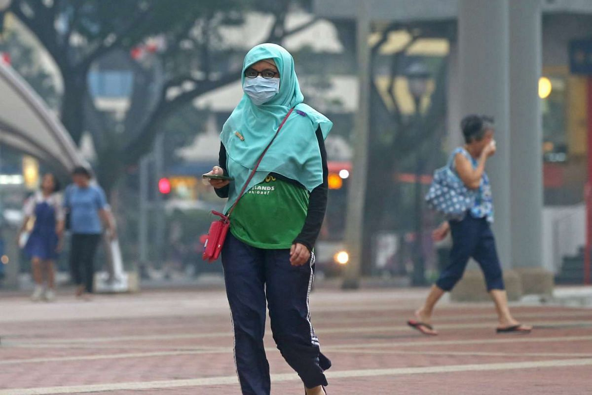 Hazy conditions on Sept 14, as people are seen wearing masks at Toa Payoh Central as the 3-hour PSI readings exceed 100 in the Unhealthy level during late afternoon.