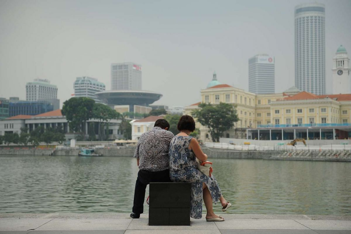 A couple sitting by Singapore River despite the Pollutent Standards Index hitting the Moderate level of 99 on Sept 14.