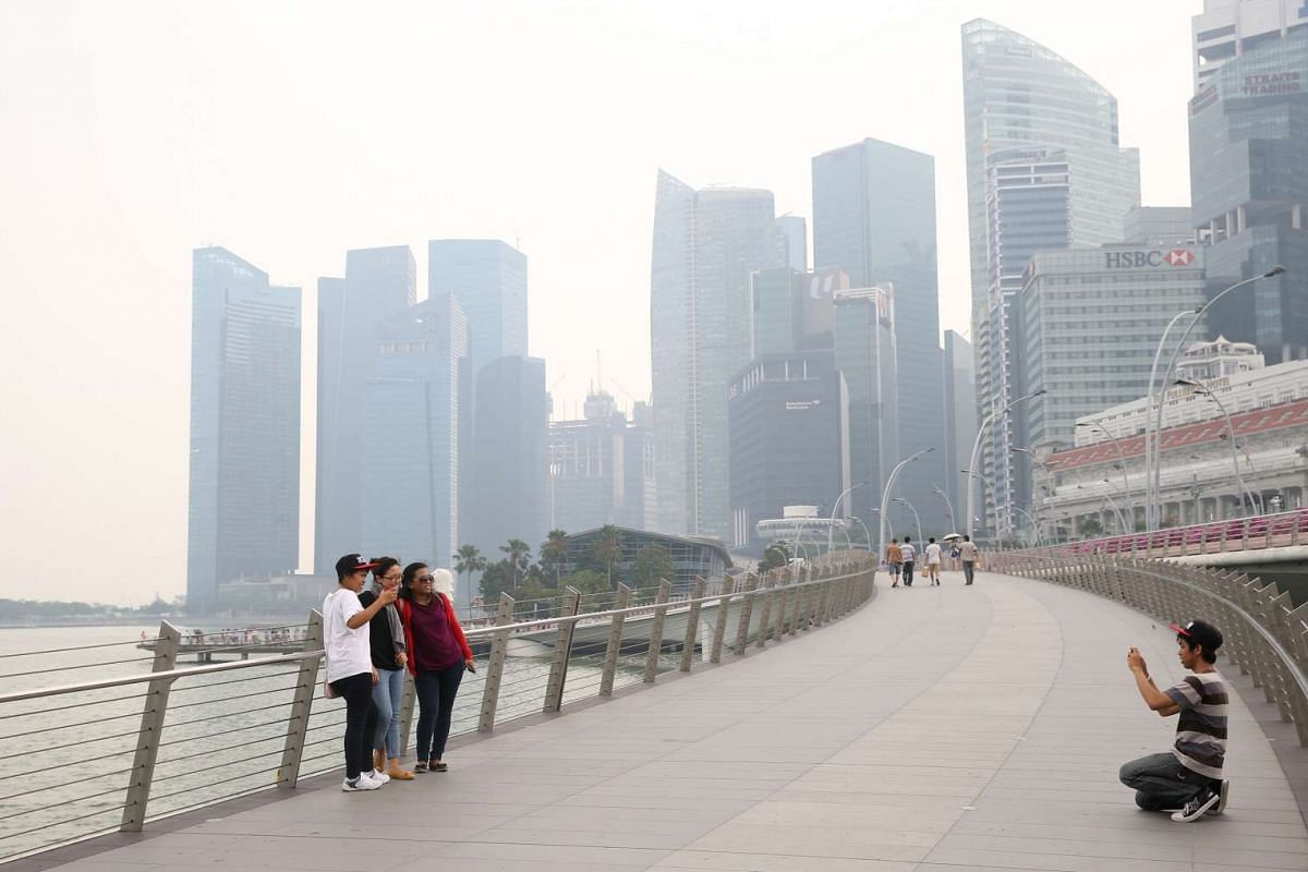 Tourists and a few joggers on Jubilee Bridge despite hazy conditions on Monday, Sept 14, with the 3-hour PSI readings at around the unhealthy level of 100, between 1pm and 2pm.