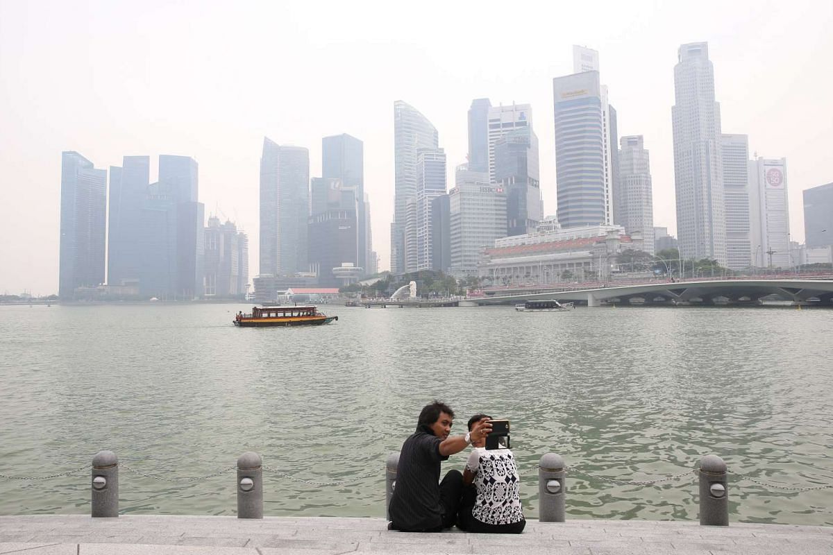 Tourists and a few joggers are seen on Esplanade outdoor theatre despite hazy conditions on Monday, Sept 14, with 3-hour PSI readings at around the unhealthy level of 100, between 1pm and 2pm. This picture was taken at 2pm.
