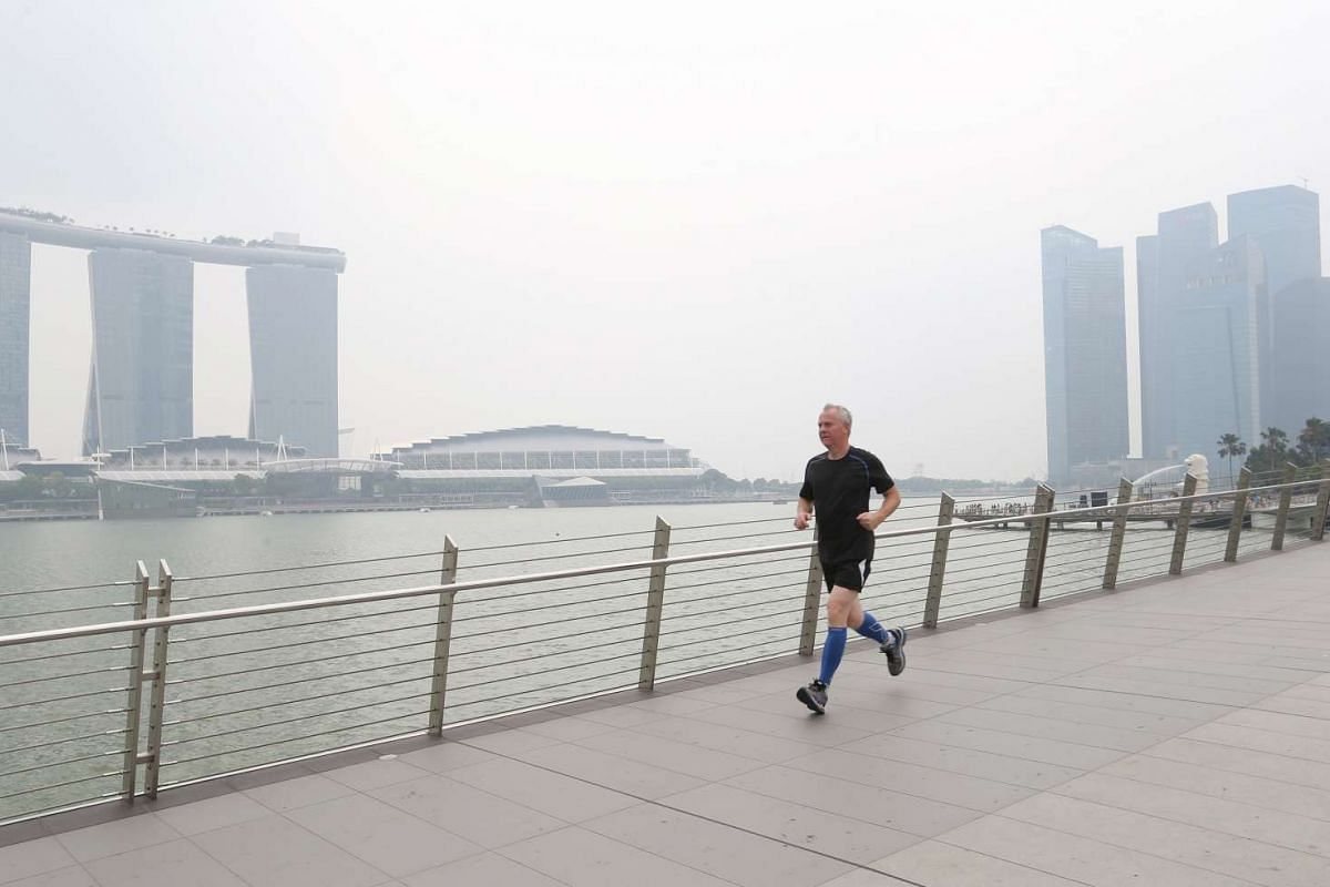Tourists and a few joggers are seen on Jubilee Bridge despite hazy conditions on Monday, Sept 14, with 3-hour PSI readings at around the Unhealthy level of 100, between 1pm and 2pm.