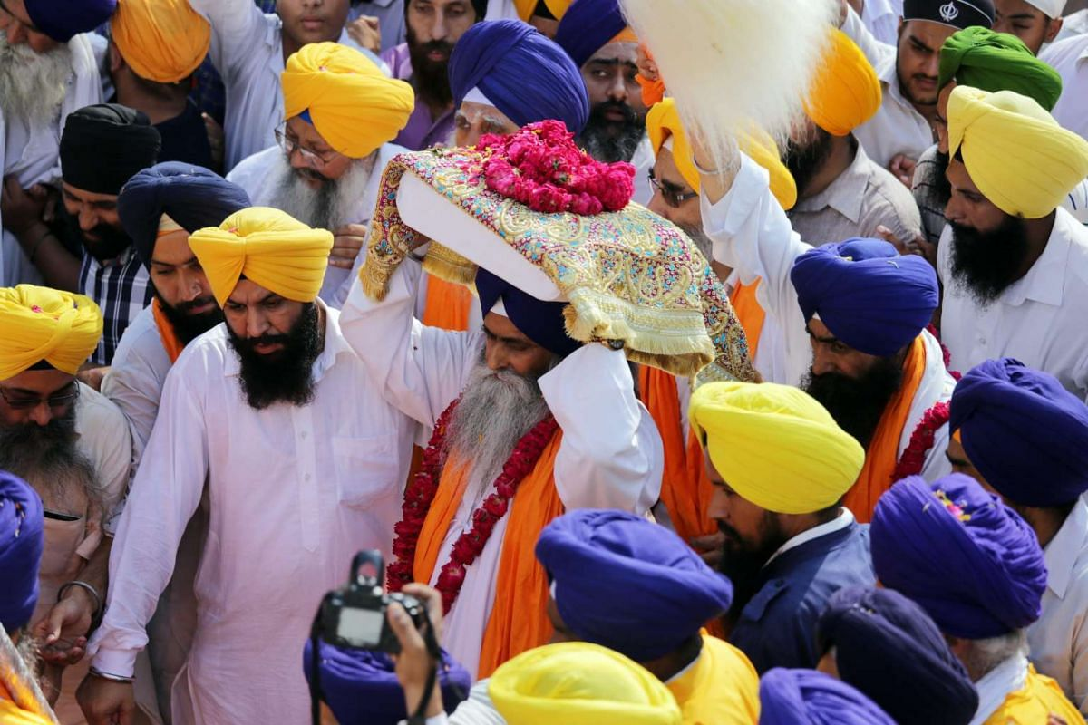 A Sikh priest carries the Sri Guru Granth Sahib Ji, the holy book of the Sikh religion, on his head at the Golden Temple, the holiest of Sikh shrines, during a religious procession in Amritsar, India, on Sept 14, 2015.