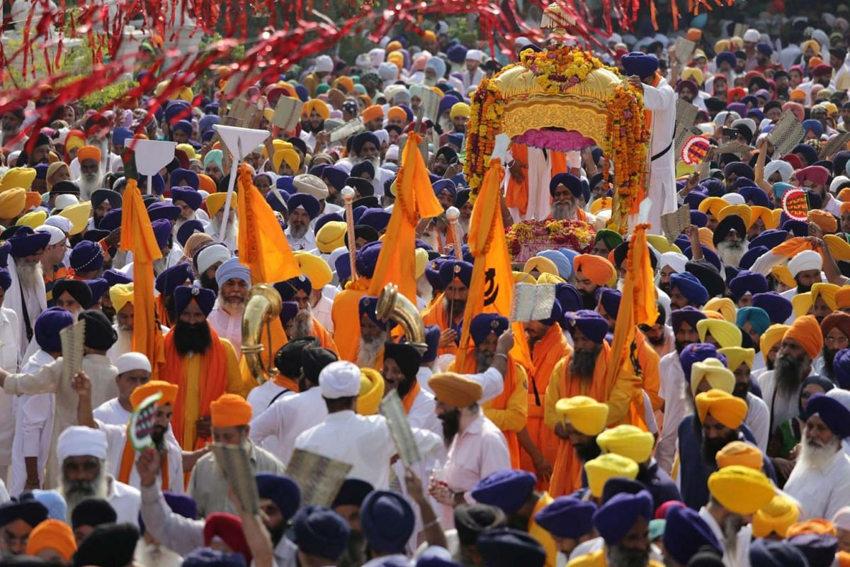 Sikh devotees carry the Sri Guru Granth Sahib Ji, the holy book of the Sikh religion, in a special golden palanquin at the Golden Temple, the holiest of Sikh shrines, during a religious procession in Amritsar, India, on Sept 14, 2015.