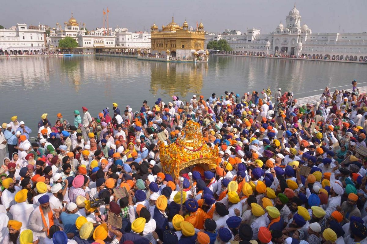 Indian Sikh devotees carry the Palki Sahib with the Guru Granth Sahib, the central religious text of Sikhism during a religious procession from Gurudwara Ramsar to Akal Takht Sahib to mark the 411th anniversary of the installation of the book at the