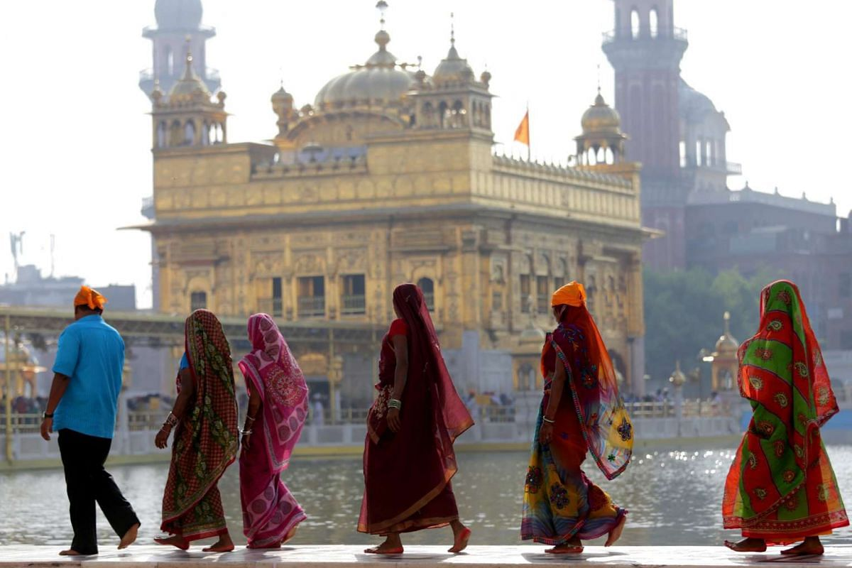 Devotees walk near the sacred pond of the Golden Temple, the holiest of Sikh shrines, in Amritsar, India, on Sept 12, 2015.
