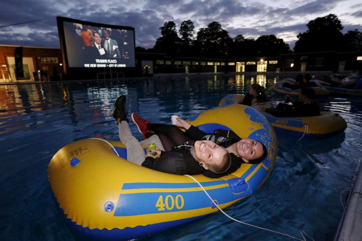 "Movie goers smile as they wait to watch a screening of Steven Spielberg's film ""Jaws"" whilst floating in inflatable dinghies at Brockwell Lido in London, Britain Thursday September 17, 2015. PHOTO: REUTERS / LUKE MACGREGOR"