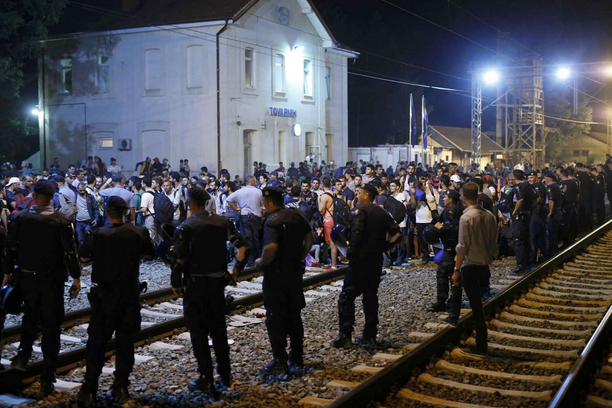 Croatian police standing guard in front of migrants at the train station in Tovarnik on Sept 17, 2015.