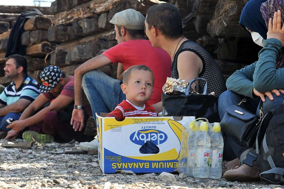 A young boy sits in a box alongside refugees resting at a railway station near the eastern Croatian town of Tovarnik on Sept 17, 2015.