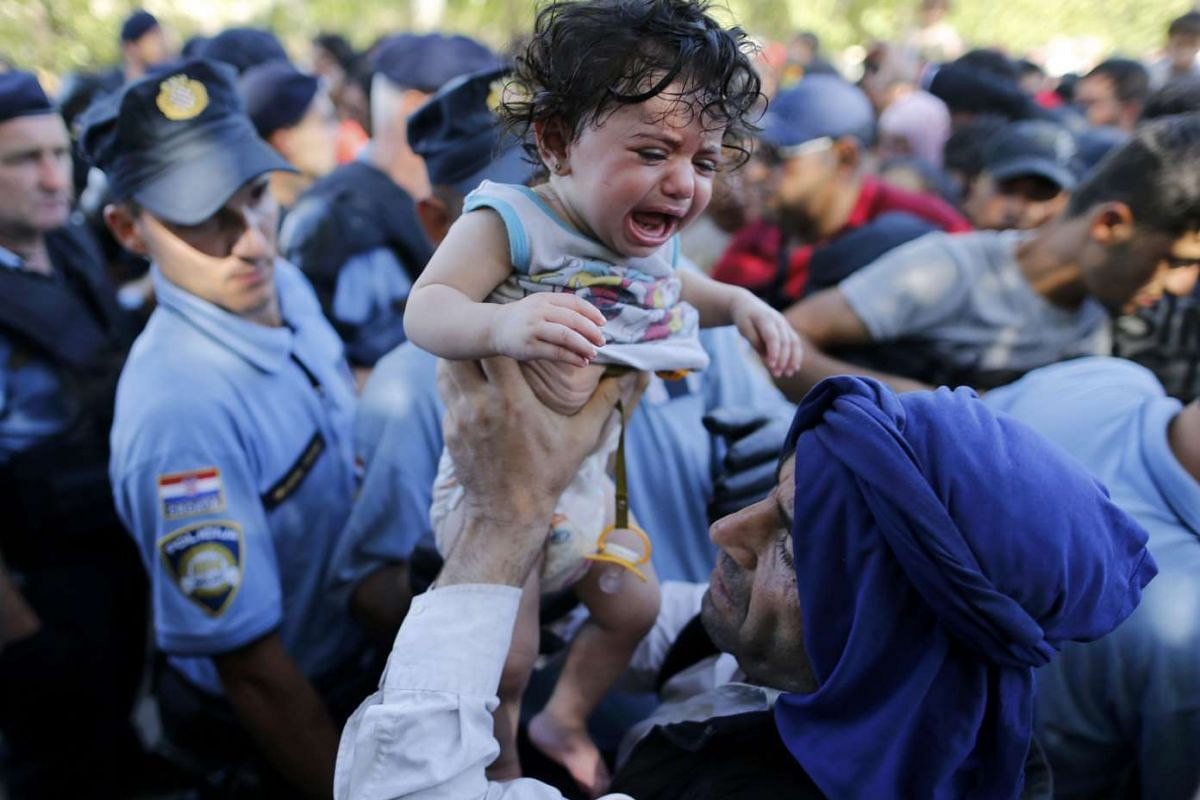 A migrant lifting a crying baby as he waits to board a bus in the Croatian town of Tovarnik on Sept 17, 2015.