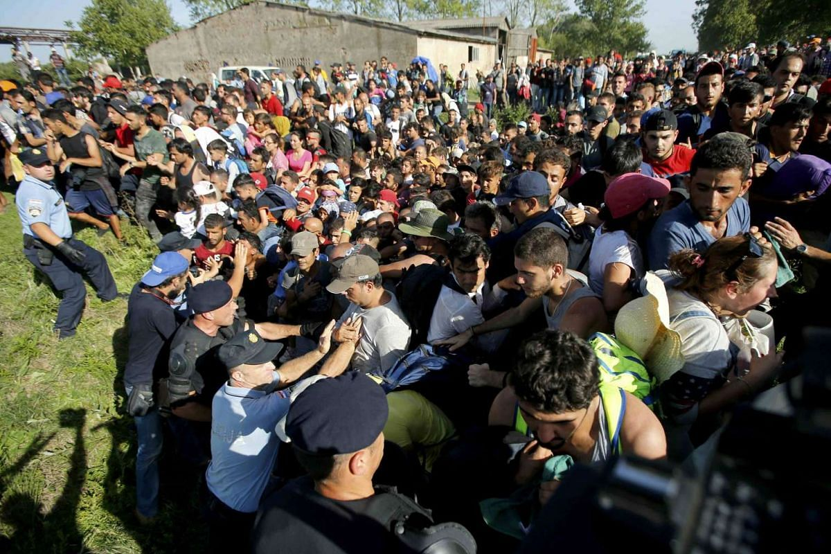 Migrants pushing against policemen during a stampede to board buses in the Croatian town of Tovarnik on Sept 17, 2015.