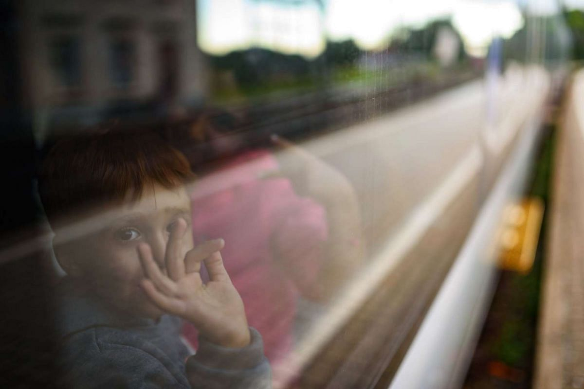 Children reacting after boarding a train to Graz at a railway station in Spielfeld on Sept 20, 2015. Some 150 migrants entered Austria from across the Slovenian border today, opening up  a new route for the thousands seeking to cross the Balkans into