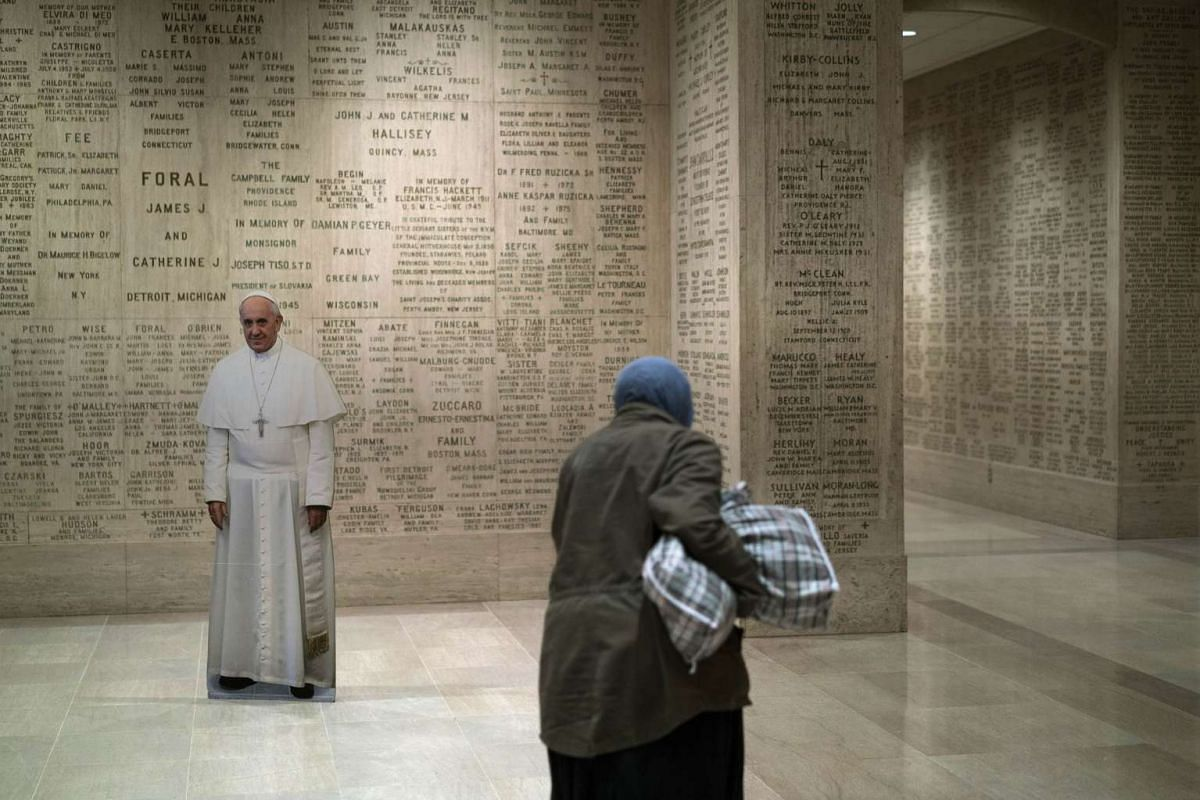 A woman walking past a cutout of Pope Francis in the crypt of the Basilica of the National Shrine of the Immaculate Conception on Sept 21, 2015, in Washington, DC.
