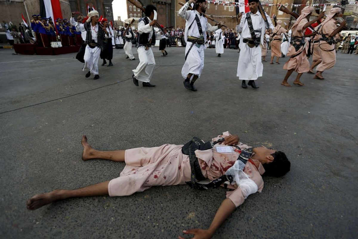 A Houthi follower with fake blood on his clothes lying on the ground to represent a victim as others perform a war dance during a ceremony marking the first anniversary of the Houthi movement's takeover of Yemen's capital Sanaa on Sept 21, 2015.