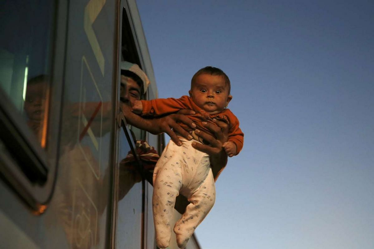 A migrant holding a baby outside the window of a train while waiting to depart from the railway station in Tovarnik, Croatia, on Sept 21, 2015. Around 29,000 people, mostly from Syria, have arrived in Croatia from Serbia in the past week after trekki