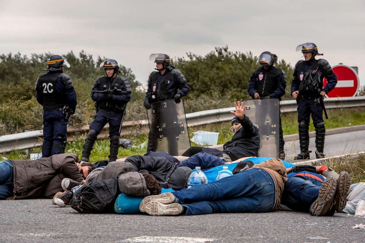 Migrants sleeping on the ground after their eviction by French police officers and gendarmes from a camp site in Calais, northern France, on Sept 21, 2015. Thousands of migrants over the summer attempted to cross the Channel Tunnel between Britain an