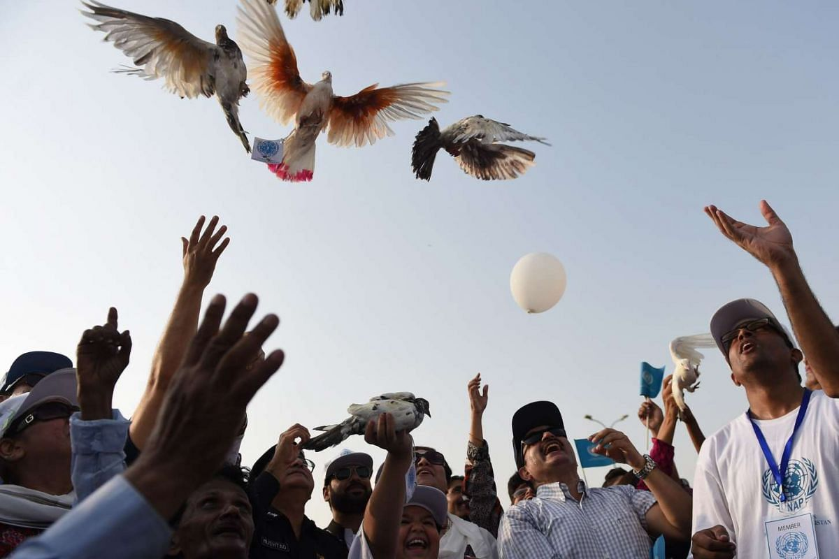 Pakistan human rights activists, residents and police officials releasing pigeons to mark the International Day of Peace in Karachi on Sept 21, 2015. The United Nation's International Day of Peace is celebrated on this day each year to recognise the