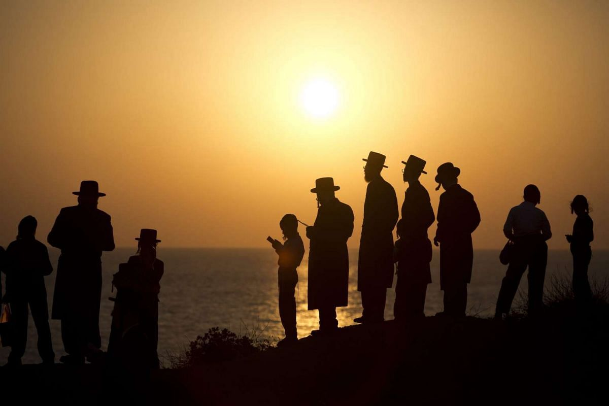 Ultra-orthodox Jews praying as they perform the Tashlich ritual at the beach  in Herzliya, outside Tel Aviv, Israel, on Sept 21, 2015. Tashlich is a ritual during which believers cast their sins into the water and the fish, and it is performed before