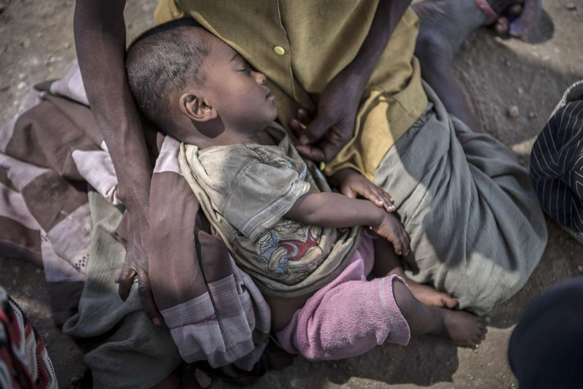 One-year-old Tovonday Neoline sleeps on his mother's lap while awaiting treatment for malnourishment at the Ambazoa Village Health Centre, Ambovombe, Madagascar on 22 September 2015. A severe food and nutrition crisis is affecting southern Madagasca
