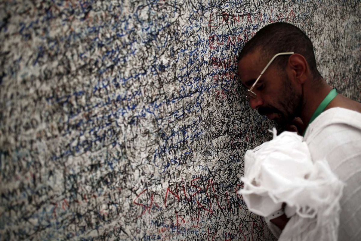 A Muslim pilgrim putting his head to a rock atop Mount Mercy on the plains of Arafat on Sept 22, 2015.