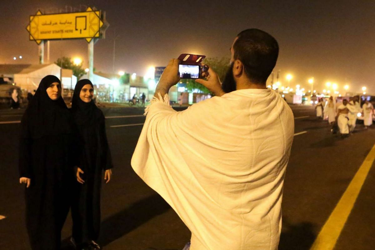 Muslim pilgrims taking photos on their way to their camp at Arafat, where they will spend the night before the first ritual of the haj pilgrimage, in Arafat, Saudi Arabia on Sept 22, 2015.